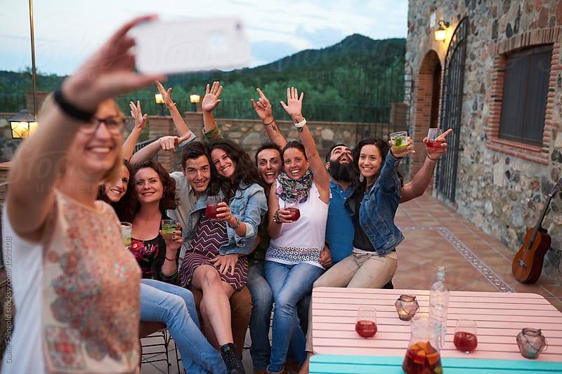 Friends taking group selfie at terrace with drinks by Guille Faingold for Stocksy United