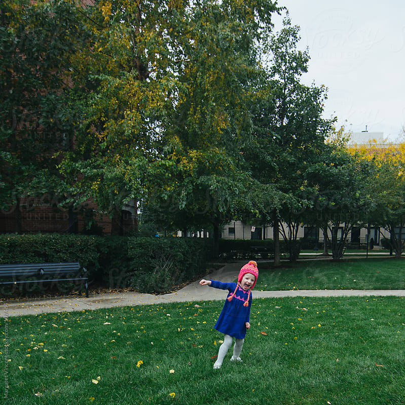 little girl plays in urban park by Margaret Vincent for Stocksy United