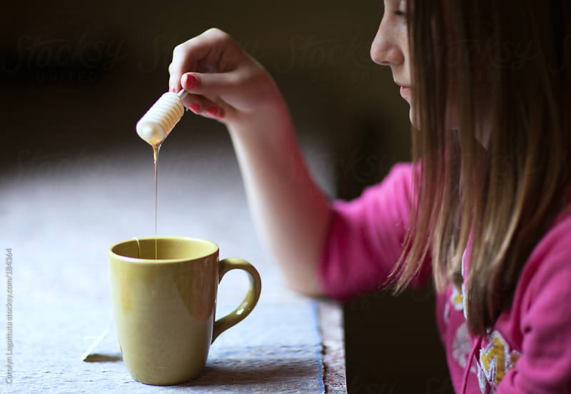 Girl drizzling honey into her hot tea by Carolyn Lagattuta for Stocksy United