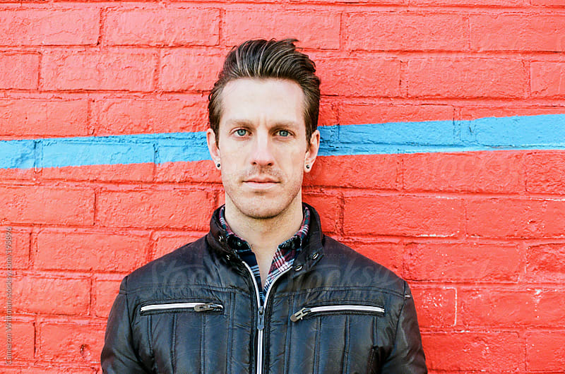 Handsome man in a puffer jacket portrait by Cameron Whitman for Stocksy United