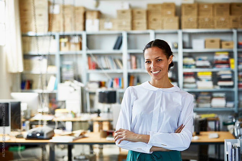 Smiling Businesswoman Standing Arms Crossed In Office by ALTO IMAGES for Stocksy United