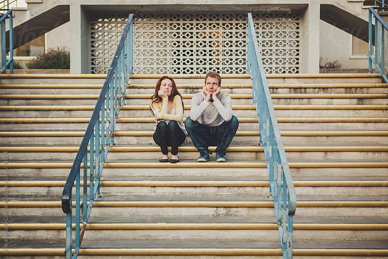 Bored couple on steps by Rob and Julia Campbell for Stocksy United