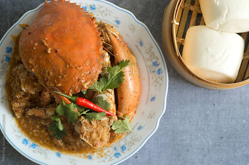 Chili crab and steamed mantao by Alita Ong for Stocksy United