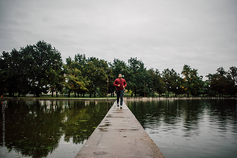 Young man running across the lake bridge by Boris Jovanovic for Stocksy United