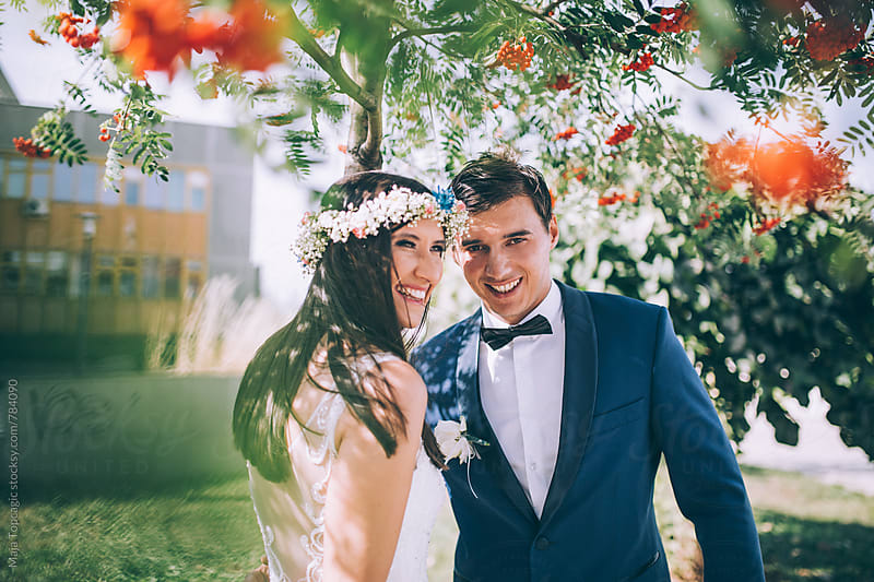 Bride and groom laughing outdoors in nature by Maja Topcagic for Stocksy United