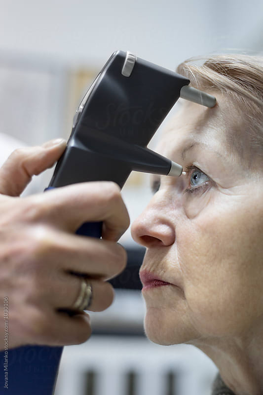 Ophthalmologist measuring eye pressure to a senior woman by Jovana Milanko for Stocksy United