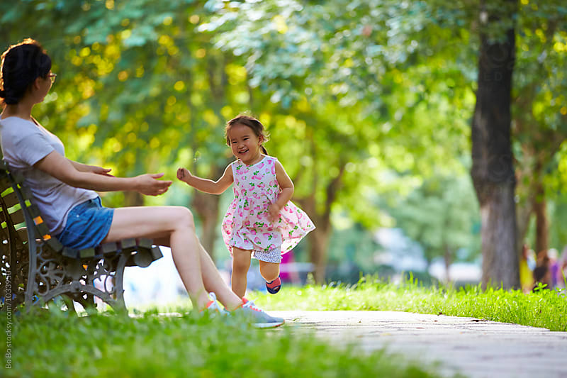 happy little asian girl with her mother in the park by Bo Bo for Stocksy United