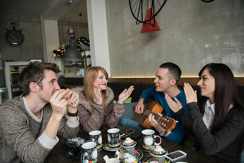Friends Enjoying Guitar in a Cafe by Mosuno for Stocksy United
