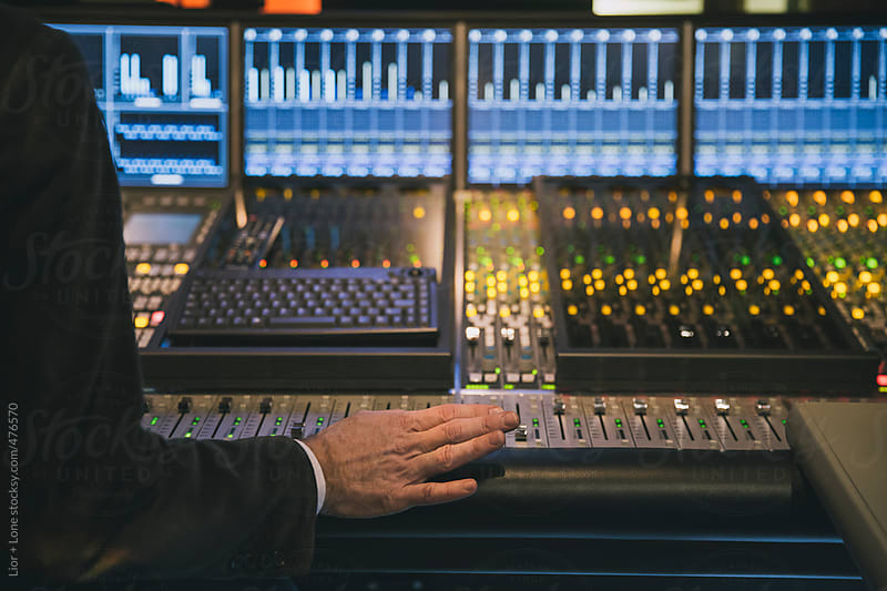 Closeup of a technician's hand in recording studio by Lior + Lone for Stocksy United