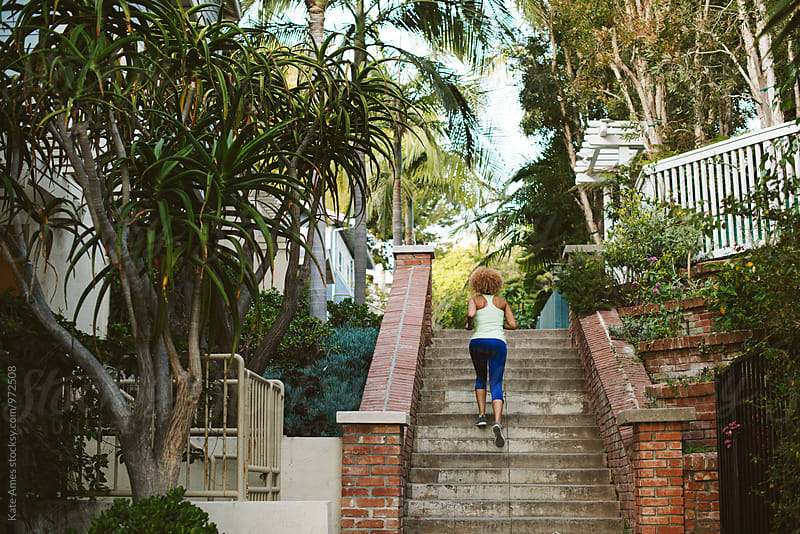 Young African American woman running stairs for exercise in California by Kate Daigneault for Stocksy United