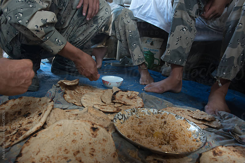 Afghan border police eating naan bread by Mick Follari for Stocksy United
