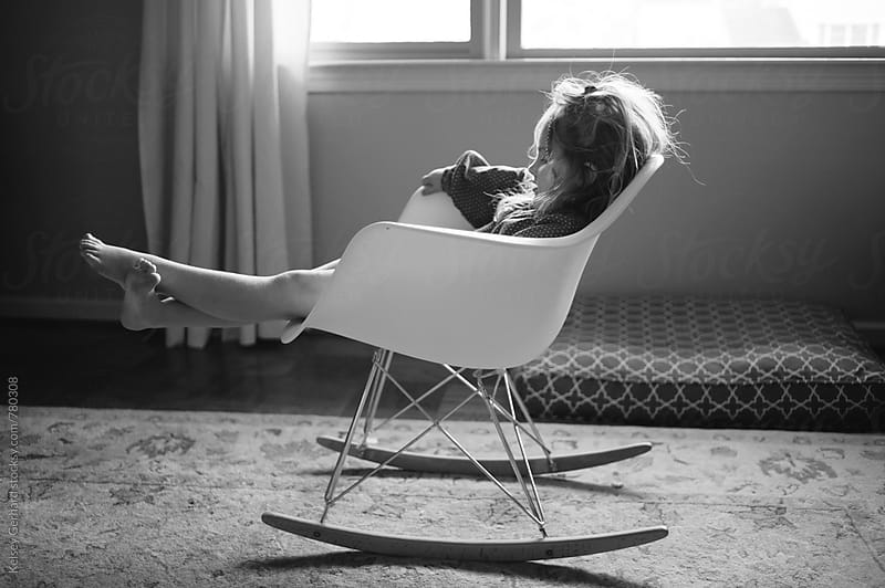 A young girl at home sits in an Eames rocking chair. by Kelsey Gerhard for Stocksy United