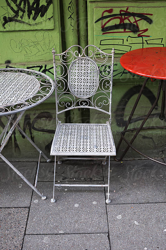 Classic metal chair and table on the pavement by Marcel for Stocksy United