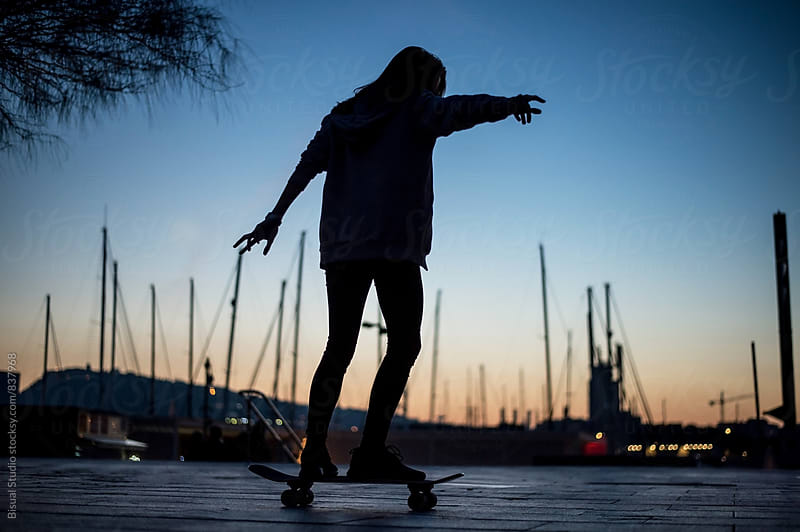 Young woman skating in the port of Barcelona at sunset by Bisual Studio for Stocksy United