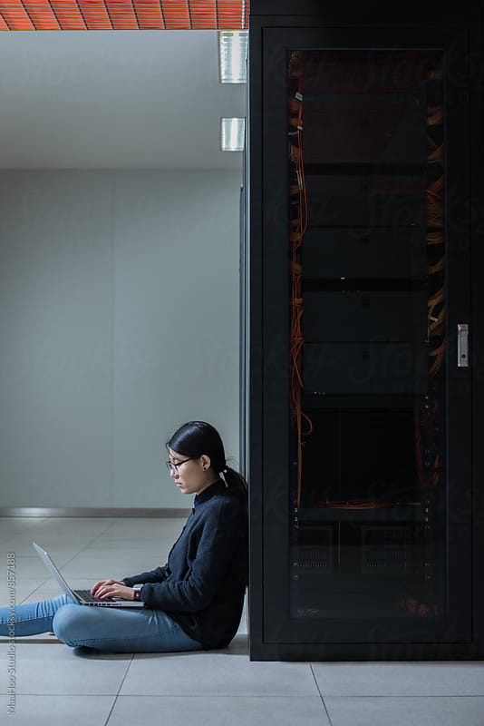 Female technician using computer in data center by MaaHoo Studio for Stocksy United