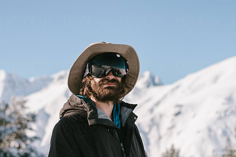 Portrait of bearded skier in snowcovered big mountain scenery by Leander Nardin for Stocksy United