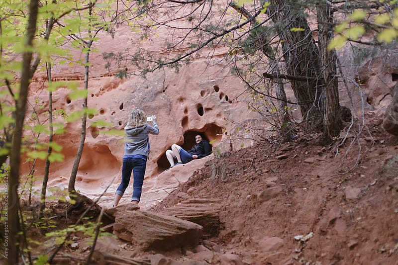 Two female friends taking pictures on a hiking trail by Amy Covington for Stocksy United