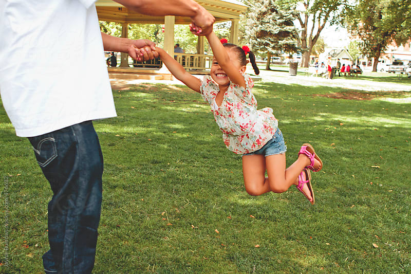 Young Father Swings Daughter in Park by Jayme Burrows for Stocksy United