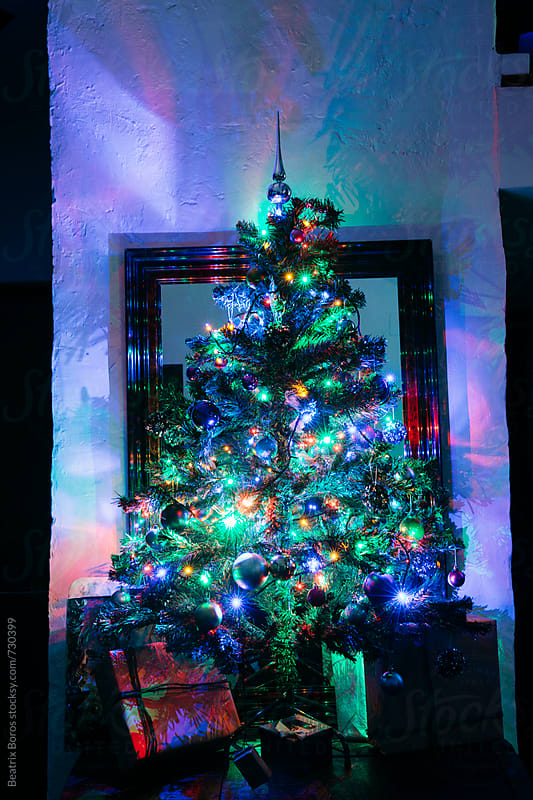 Illuminated Christmas tree with Christmas gift boxes by Beatrix Boros for Stocksy United