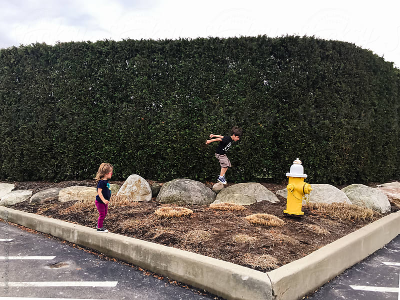 kids playing on side of parking lot by Maria Manco for Stocksy United