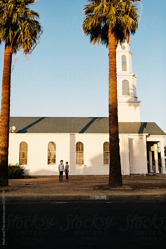 Man and woman standing by white church by Matt and Tish for Stocksy United