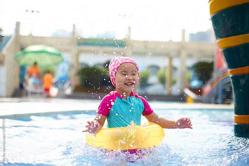 lovely little asian girl having fun in the swimming pool by Bo Bo for Stocksy United