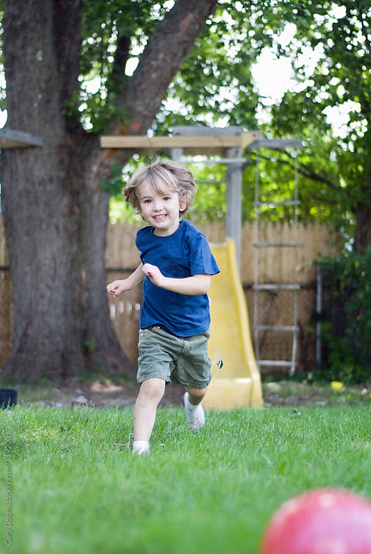 Young child runs around in his backyard by Cara Dolan for Stocksy United