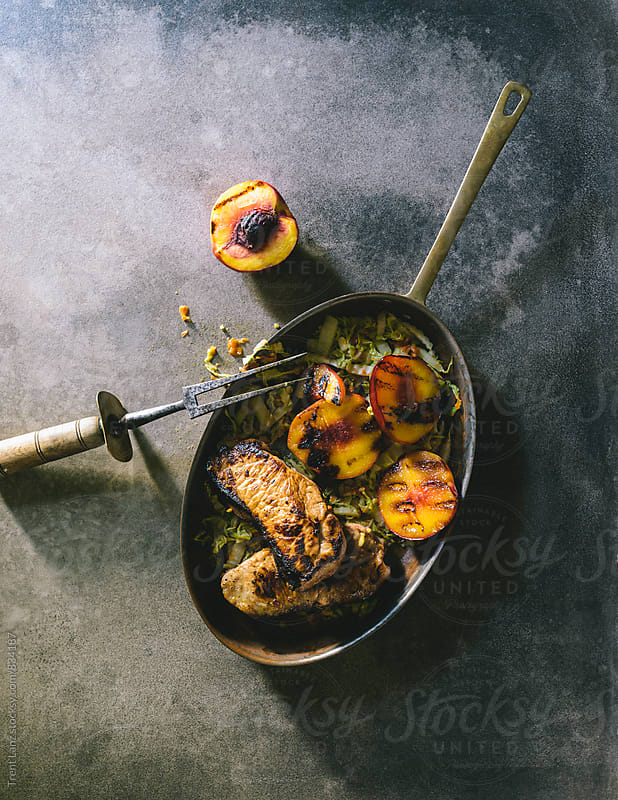Paleo honey glazed pork chops with nectarines by Trent Lanz for Stocksy United