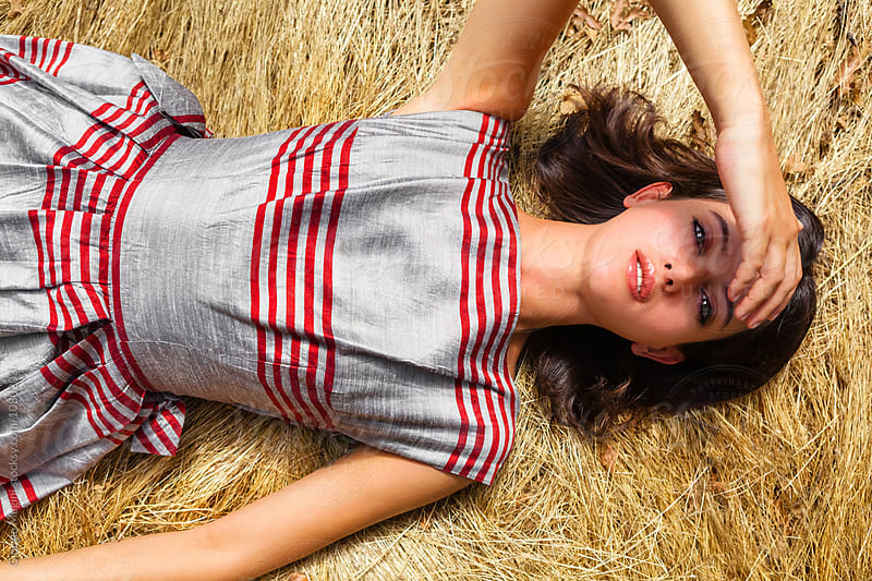 Retro Styled Woman Lying on Hay by Giorgio Magini for Stocksy United