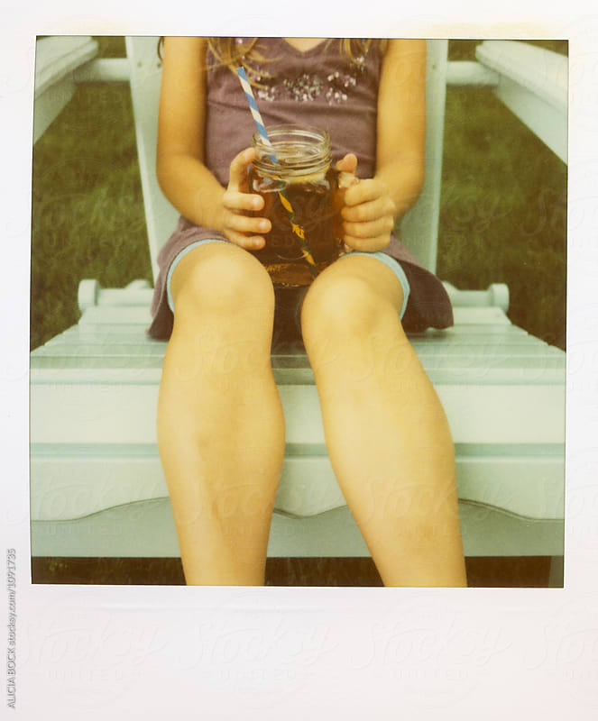 Anonymous Girl Sitting In An Adirondack Chair With Iced Tea Photographed On Expired Polaroid Film  by ALICIA BOCK for Stocksy United