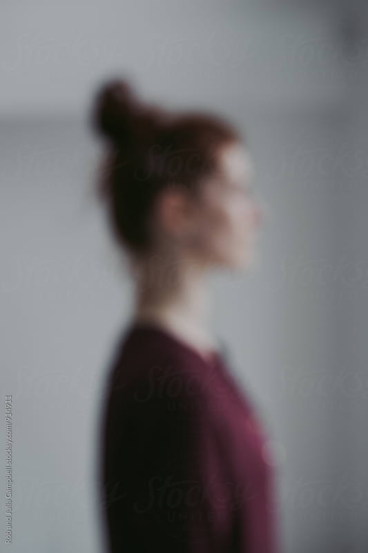 Blurry profile image of red head in white room by Rob and Julia Campbell for Stocksy United