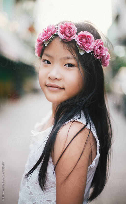 Beautiful little girl portrait with pink rose headband by Nabi Tang for Stocksy United
