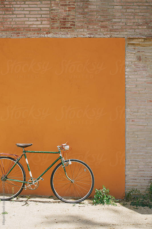 Old bicycle standing on a orange  wall by Miquel Llonch for Stocksy United