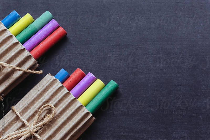 Packaged crayons on a chalk board by Paul Phillips for Stocksy United