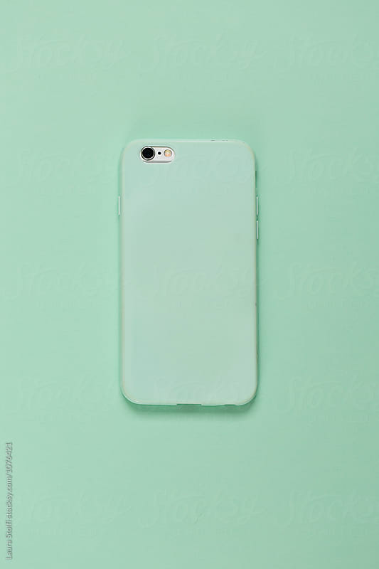 Rear sight of mobile phone with mint cover on mint background by Laura Stolfi for Stocksy United