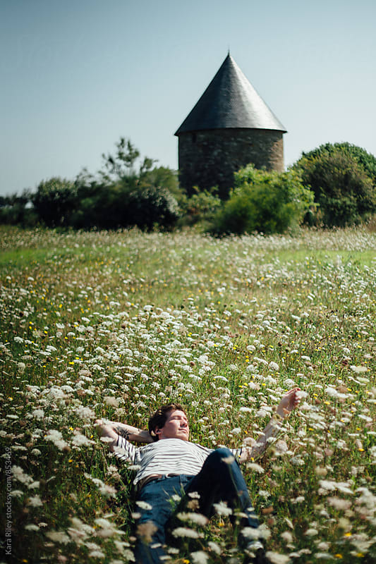 Lying in a meadow by Kara Riley for Stocksy United