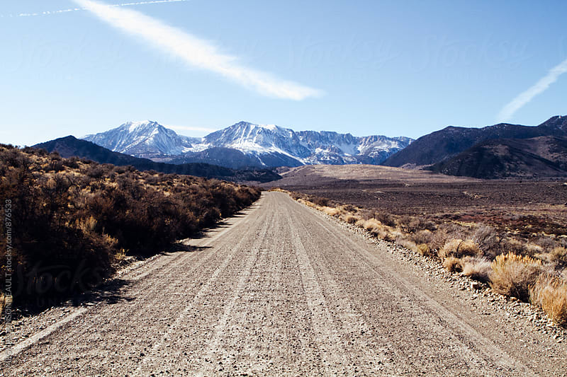 Dirt Road on Sunny Day with Snowy Winter Mountain Backdrop by Meg Pinsonneault for Stocksy United
