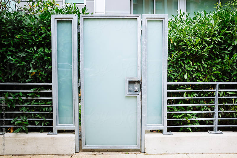 A modern door entry with a natural green privacy wall. by J Danielle Wehunt for Stocksy United