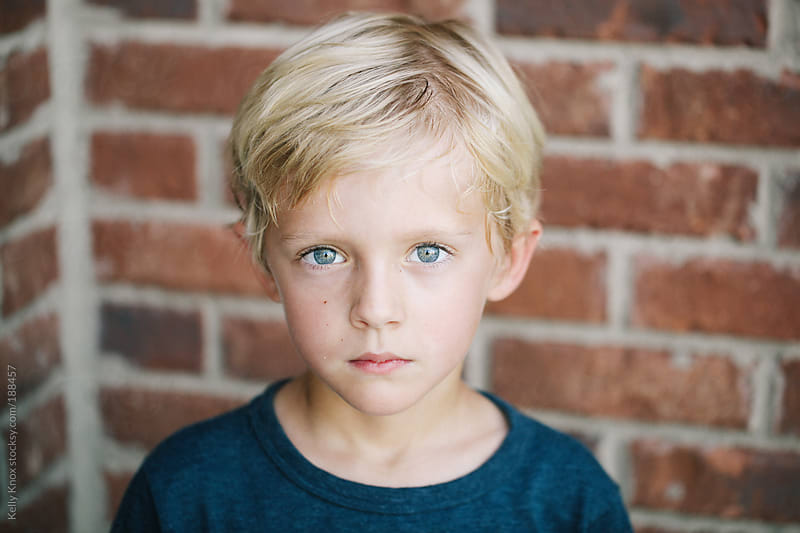 a serious boy in front of a brick wall by Kelly Knox for Stocksy United