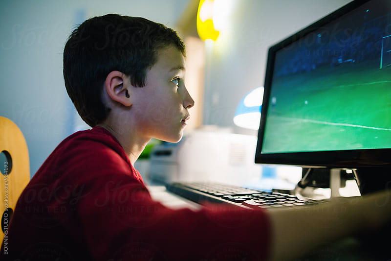 Little boy playing video games on the computer. by BONNINSTUDIO for Stocksy United