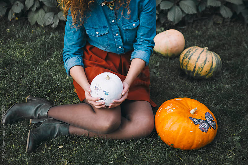Woman holding white pumpkin sitting on grass by Danil Nevsky for Stocksy United