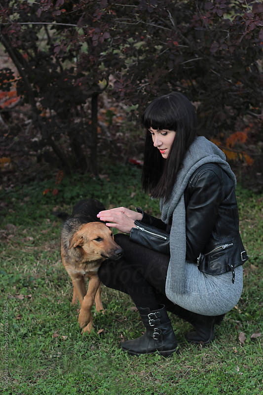 Young woman cuddling stray dog by Branislava Živić for Stocksy United