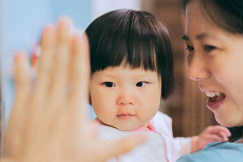 baby girl with her mother by Xunbin Pan for Stocksy United