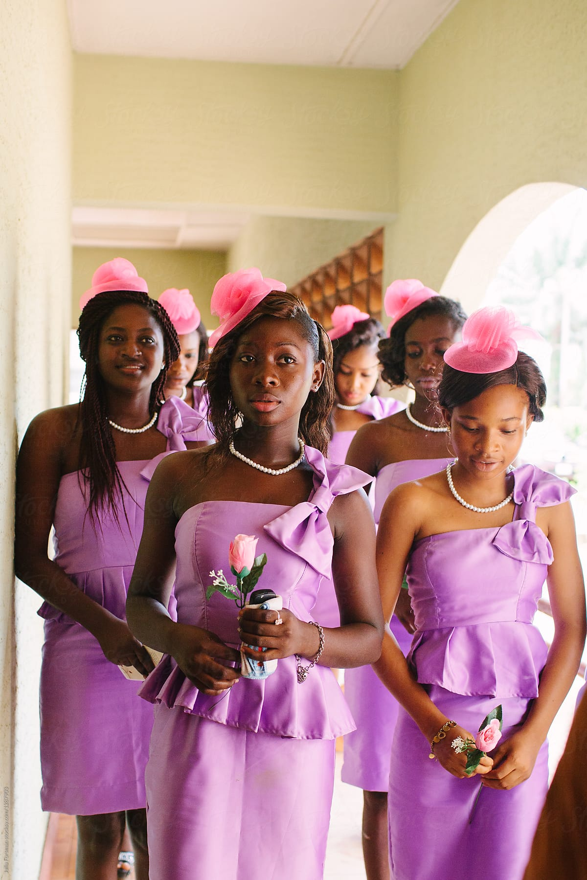 dfcca78f25c Stock Photo - A Group Of Six African Bridesmaids Wearing Purple Dresses And  Pink Hats Stand Waiting Before The Wedding.