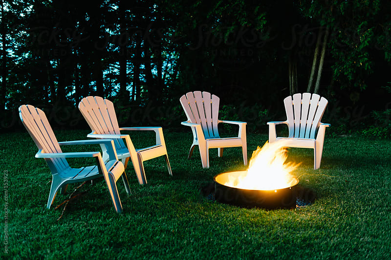 4 empty chairs around a campfire. by Jen Grantham for Stocksy United