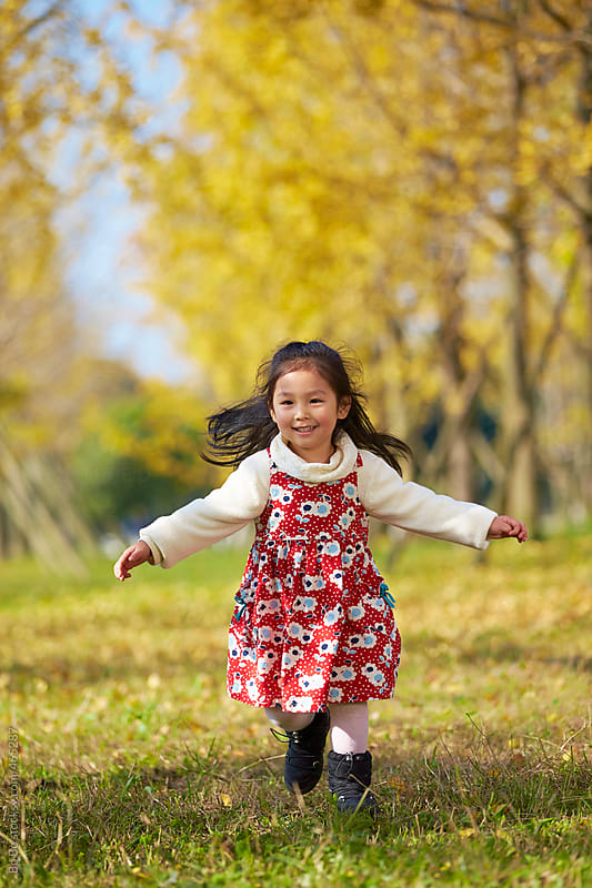 lovely little girl playing in the autumn ginkgo woods by Bo Bo for Stocksy United