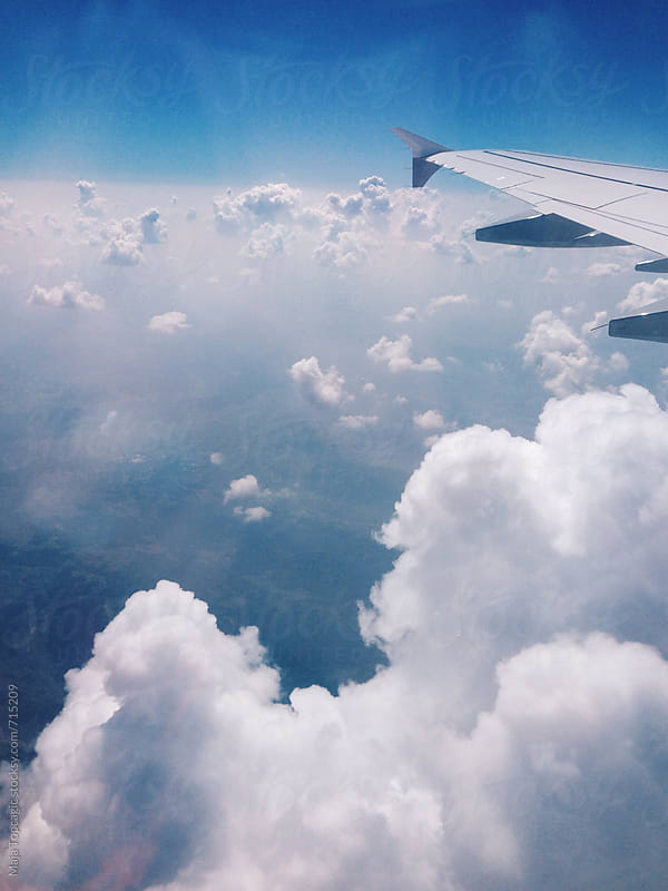 Clouds in the sky through aeroplane window by Maja Topcagic for Stocksy United
