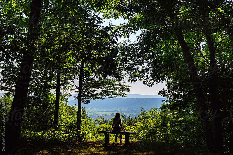 silhouette of girl on a bench overlooking the mountains by Deirdre Malfatto for Stocksy United