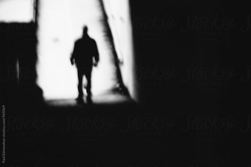 Blurred view of man walking down dark alley at night by Paul Edmondson for Stocksy United