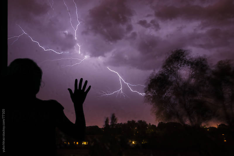 Anxious woman on a stormy night with lightning by yuko hirao for Stocksy United